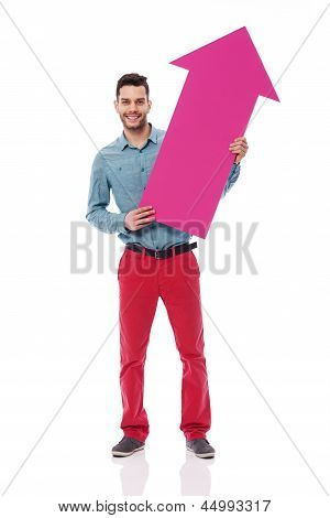 Smiling man holding pink arrow sign