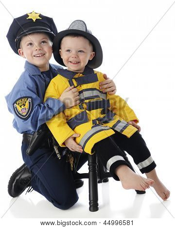 Two young brothers posing together -- an elementary boy in a policeman's outfit, the toddler dressed as a fire fighter.  On a white background.