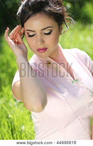 Portrait Of Beautiful Brunette Young Woman Resting Over Green Grass