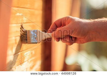 Male hand painting wooden wall
