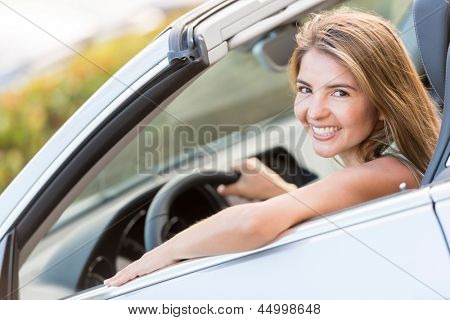 Beautiful woman driving a car and looking very happy