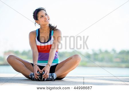 Beautiful thoughtful woman working out outdoors and smiling