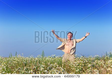 The happy young man in the field of chamomiles..