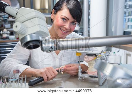 Technician In A Dental Lab Or Workshop Working Under A Microscope
