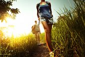 image of greenery  - Two young ladies walking with backpacks on a thin path through a lush tropical meadow - JPG