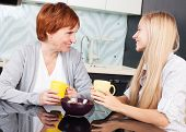 image of only mature adults  - Happy adult woman with daughter on kitchen - JPG