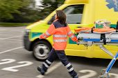 stock photo of ambulance car  - Blurry paramedics in hurry pulling gurney next to ambulance car - JPG