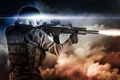 stock photo of gun shot  - assault soldier with rifle on apocalyptic clouds - JPG