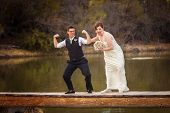 stock photo of dock a pond  - Same sex female couple having fun on dock near lake - JPG