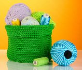 Colorful yarn for knitting in green basket on orange background