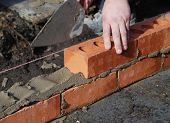 foto of stone house  - Construction worker laying bricks showing trowel and guideline - JPG