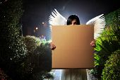 picture of garden eden  - Angel woman with white wings holding blank cardboard message board poster in night garden - JPG