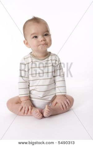Baby Boy Sitting On The Floor With An Odd Expression