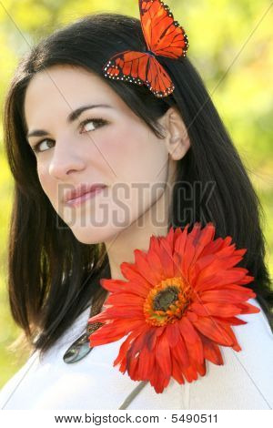 Woman With Butterfly And Red Flowers In Park