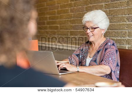 Senior woman using laptop in coffeeshop
