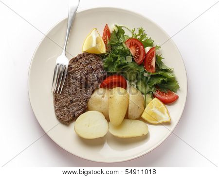 Pan-grilled pepper minute steak served with a salad of fresh leaves, tomato, cucumber and lemon with boiled new potatoes