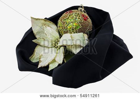 Xmas Ball And Flower Cradled On A Black Cloth