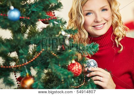 Pretty female looking at camera out of decorated firtree