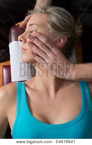 Chiropractor adjusting neck muscles young patient