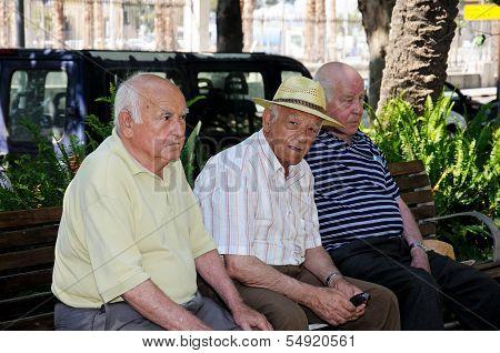 Three men sitting on a park bench, Malaga, Spain.