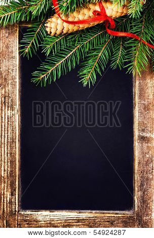 Christmas  Tree Branch On  Vintage Blackboard With Cone And Red Ribbon. Retro Slate Chalk Board With
