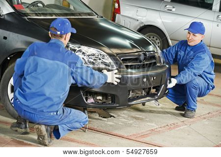Two repairman mechanics matching automobile body bumper on damaged car at repair service station