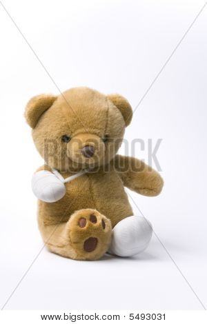 Teddy Bear With Two Broken Legs On White Background