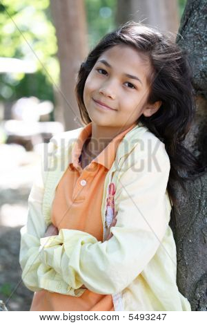 Young Girl Relaxing Against Tree