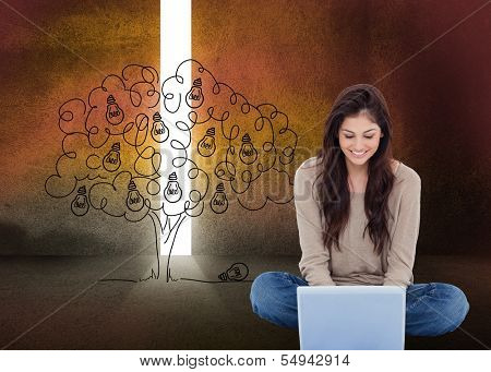 Composite image of beautiful smiling brunette sitting on floor using laptop