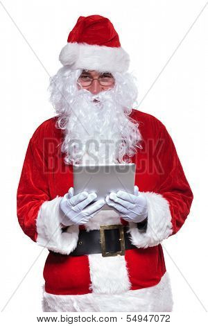 portrait os santa claus holding and reading on a tablet pad computer, on white background