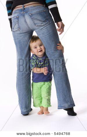 Little Toddler Boy Is Standing Between His Parents Legs