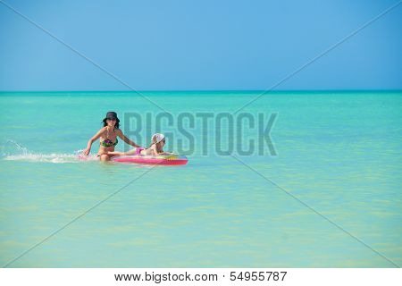 Mother With Young Daughter On An Air Mattress In The Sea