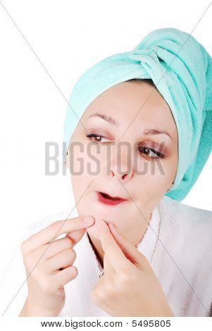 Una chica guapa encontrar un acné en la barbilla