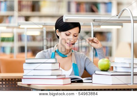 Woman with green apple surrounded with piles of books reads sitting at the desk at the library. Academic achievement