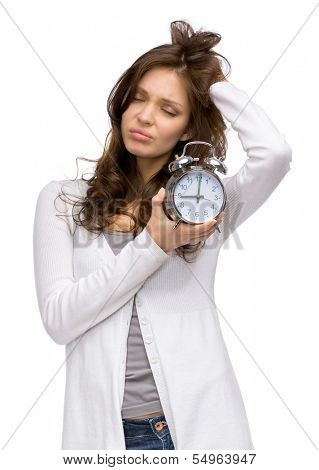Half-length portrait of tired woman keeping alarm clock, isolated on white