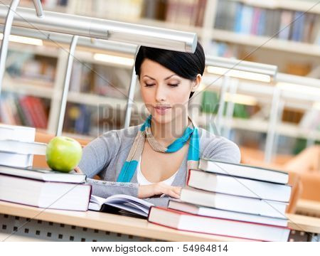 Woman with green apple surrounded with piles of books reads sitting at the table at the library. Information overload