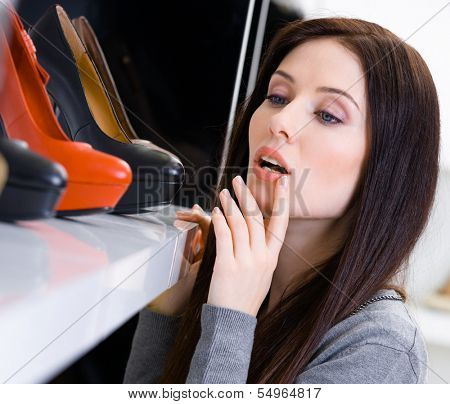 Close up of woman choosing a pair of shoes in shopping center
