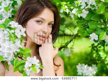 Portrait of young woman touches her face standing near the flowered tree in the park. Concept of youth and natural beauty