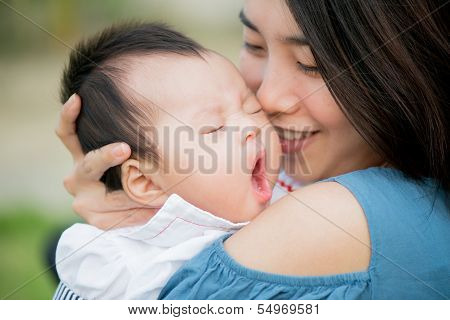 Happy Asian Mother Kissing The Cute Baby Yawning