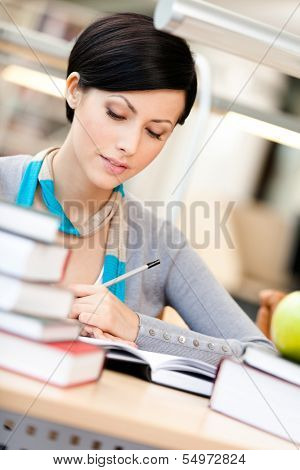 Woman with green apple surrounded with piles of books reads sitting at the table at the library. Academic achievement