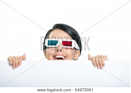 Girl in 3D spectacles peeps out from behind the copyspace, isolated on white