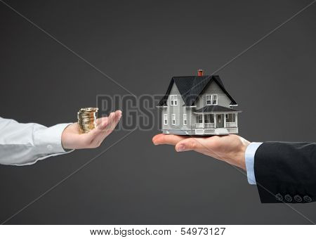 Close up of two hands. One with coin money, another one with little house. Concept of deal and real estate