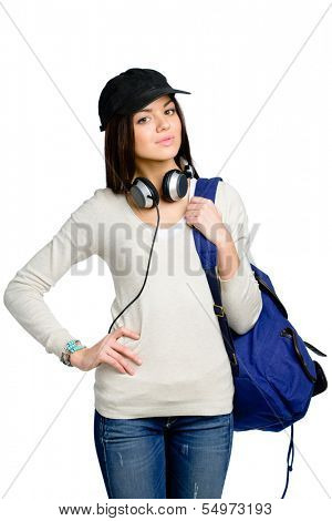 Half-length portrait of teenager with earphones and rucksack in black peaked cap, isolated on white