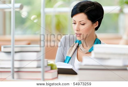 Woman surrounded with piles of books reads sitting at the table at the library. Information concept
