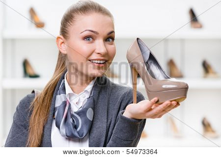 Portrait of woman keeping coffee-colored shoe in shopping center against the showcase with pumps