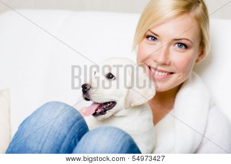 Close up of woman in white sweater with white puppy sitting on her knees