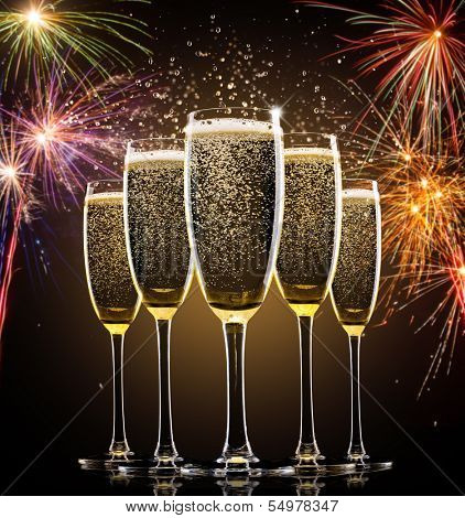 Glasses of champagne with firework on background