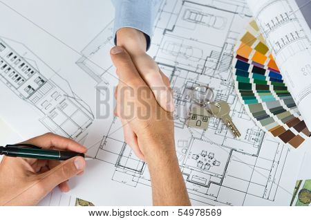 New home agreement! High View Of Two People Shaking Hand With Blueprint Below