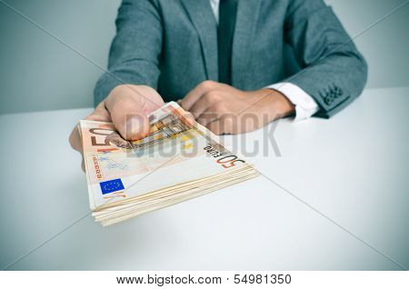 a man wearing a suit sitting in a desk with a wad of euro bills in his hand