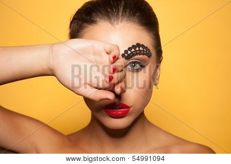 Beauty portrait of a beautiful woman covering her right eye with the back of the hand wearing avant-garde makeup